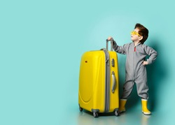 Independent kid boy in gray overall, yellow rubber boots and sunglasses stands at big roller bag wheeler looks forward up at copy space over blue background. Travelling concept