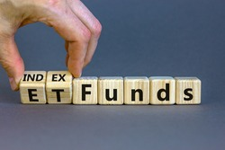 Index funds vs ETF symbol. Businessman turns a cube and changes words 'ETF, Exchange-Traded Fund' to 'Index funds. Beautiful grey background, copy space. Business and ETF vs index funds concept.