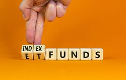 Index funds vs ETF symbol. Businessman turns a cube and changes words 'ETF, Exchange-Traded Fund' to 'Index funds. Beautiful orange background, copy space. Business and ETF vs index funds concept.
