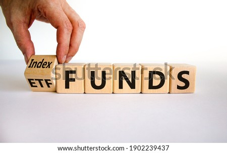 Index funds vs ETF symbol. Businessman turns a cube and changes words 'ETF' to 'Index funds. Beautiful white background, copy space. Business and ETF and index funds concept. Stock fotó ©