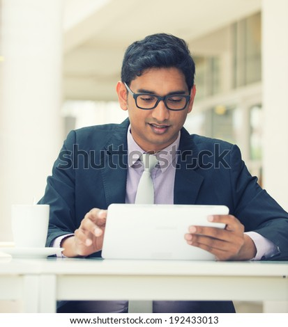 india business man on a tablet computer with vintage filter