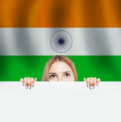 India concept. Happy woman with white paper on the India flag background. Travel and learn hindi language