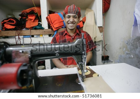 INDIA - FEB 26: Smiling textile worker in a small factory in Old Delhi on February 26, 2008 in Delhi, India. Many small factories provide the West with their clothes.