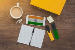 india flag, notebook, textbook, smartphone and wireless headphones on a wooden desktop, hindi foreign language learning concept
