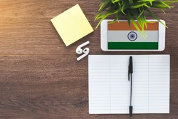india flag on gadget, wireless headphones, notebook for writing new words, place for text, learning concept