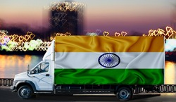 India flag on the side of a white van against the backdrop of a blurred city and river. Logistics concept