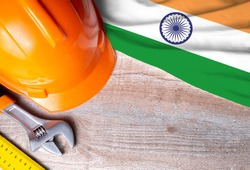 India flag with different construction tools on wood background, with copy space for text. Happy Labor day concept.