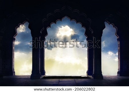 Indian arch silhouette in old temple at dramatic sunset sky with light hole in the clouds #206022802