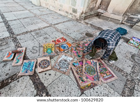 Indian artist sells paintings in front of the Santo Domingo Church - Oaxaca, Mexico