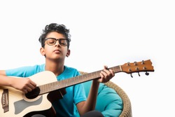 Indian asian boy playing acaustic guitar while sitting against white background or brick wala on chair