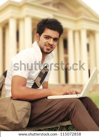 Indian Asian college student working on laptop computer in campus