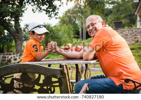 Indian/Asian kid and Grandfather Arm wrestling and having fun