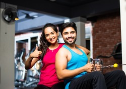 Indian asian Young couple is working out in the gym. Attractive woman and handsome fit man are training in modern gym - health and fitness concept