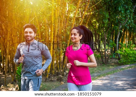 Indian asian young Couple jogging, running, exercising or stretching outdoors in park or nature Stock foto ©