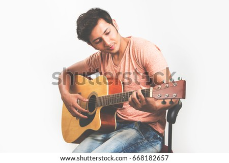Indian/Asian young man playing Guitar, sitting against white background #668182657