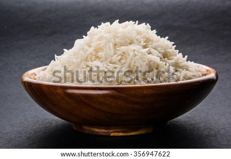 indian basmati rice, pakistani basmati rice, asian basmati rice, cooked basmati rice, cooked white rice, cooked plain rice in wooden bowl over black background