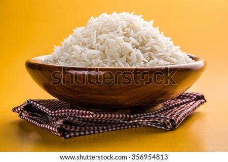 indian basmati rice, pakistani basmati rice, asian basmati rice, cooked basmati rice, cooked white rice, cooked plain rice in wooden bowl over yellow background #356954813