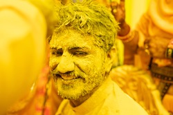 Indian Beard Man In yellow Dress With Full Face & Hair covered with yellow color with smile