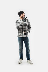 Indian bearded man in winter clothing drinking hot tea / coffee, standing isolated over white background