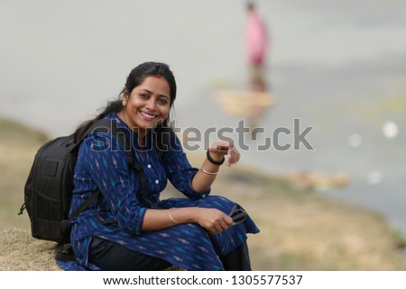 Indian beautiful and young urban woman is sitting on a hilly green grass landscape. Indian lifestyle #1305577537