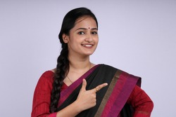 Indian beautiful woman wearing black color saree pointing finger to her left side infront of white background.
