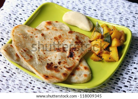 Indian Bengali breakfast plate with paratha, potato sabzi and sweet