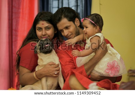 Indian Bengali Mom, dad, little girl and their family pet pug dog is sharing happy moments together Indian lifestyle