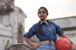 Indian Bengali teenager girl in blue jeans top and jeans hot pants is standing with a orange basketball on the rooftop. Indian lifestyle