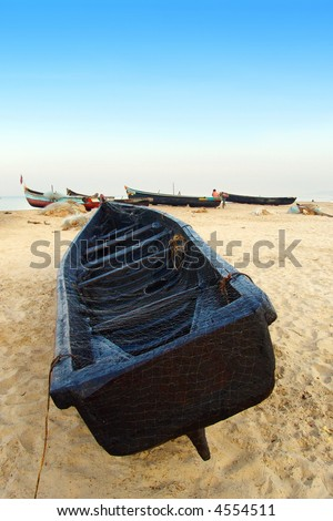 Indian boat laying on the beach covered with fishing net.