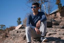 Indian boy model sitting on rocks wearing blue shirt and light grey pant.