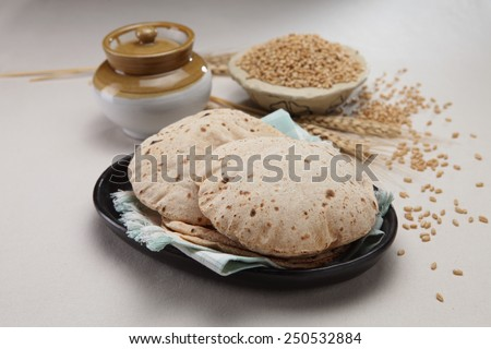 indian bread with wheat grains in background #250532884