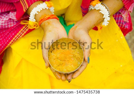 Indian Bride holding Turmeric paste or haldi paste in hand in a Hindu wedding ceremony.