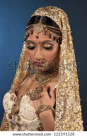 Indian bride posing for the camera against blue background