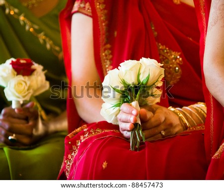 indian bridesmaids in saris holding bouquets of white roses