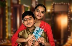 Indian Brother give gift to sister on Raksha Bandhan on dark background