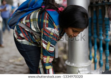 Indian brunette lady with a back pack is trying to buy and bargain fruits from a street vendor. Indian lifestyle #1334970320
