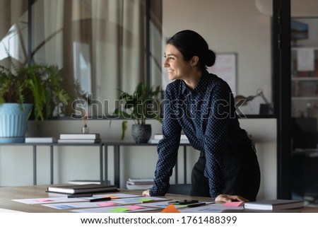 Indian business coach accomplish preparation for seminar feel satisfied looking in distance. Motivated enthusiastic employee work on project research statistics take break standing in office boardroom
