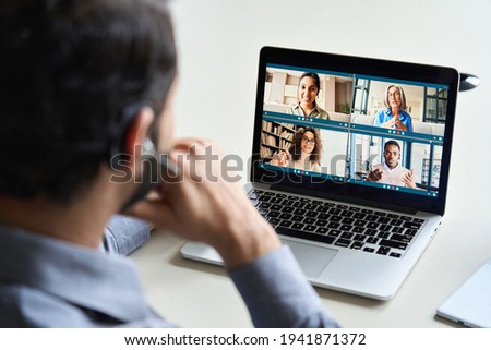 Indian business man wearing headset having virtual team meeting on video conference call using laptop work from home office talking to diverse group in remote online distance chat. Over shoulder view