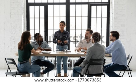 Indian business trainer teach multi-ethnic members during training seminar activity, coach stand in front of staff speaking about corporate goals, methods to succeed them. Negotiations meeting concept