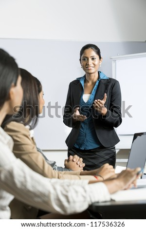Indian business woman giving a presentation for her business colleagues.