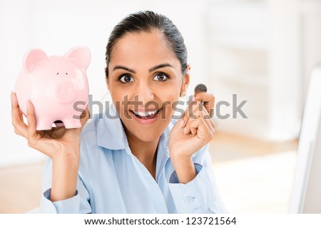 Indian business woman saving money piggy bank