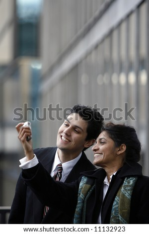 Indian business woman showing her male colleague something funny on her cell phone outside an office building
