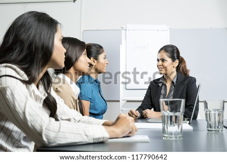 Indian business woman sitting talking with her colleagues in a meeting