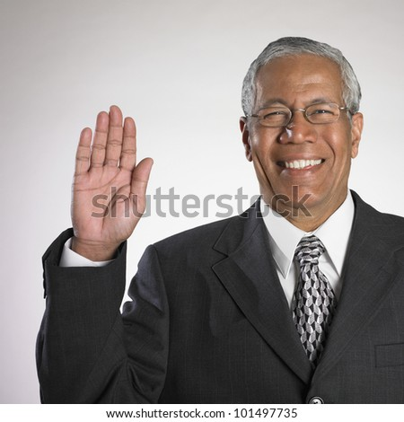 Indian businessman holding up right hand