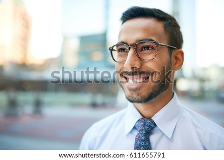 Indian businessman smiling confidently with cityscape background