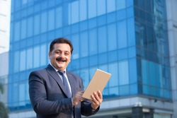Indian businessman using digital tablet in city
