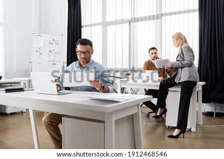 Indian businessman working with documents and laptop near colleagues in office stock photo