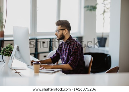 Indian Businessman working with papers and computer working at office