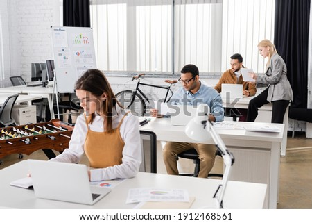 Indian businessman working with papers and laptop near multiethnic colleagues on blurred background stock photo