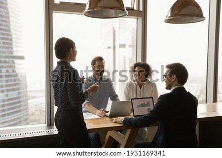 Indian businesswoman mentor leading corporate meeting in modern office with panoramic windows, boardroom, smiling colleagues sharing ideas, business partners discussing project strategy, negotiating